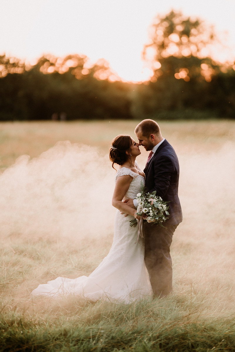 Bride and groom look at each other, in the middle of a field with smoke effect around them