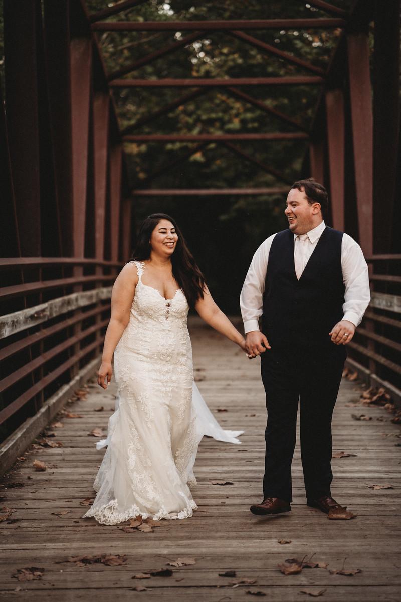 Bride and groom walk across a bridge holding hands