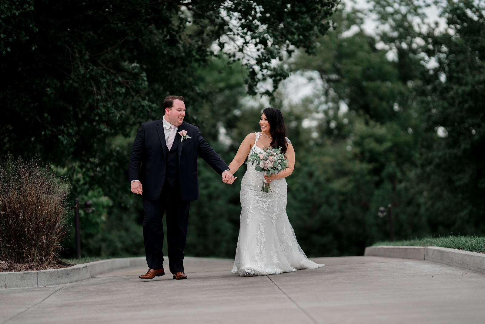 Bride and groom walk together holding hands and smiling