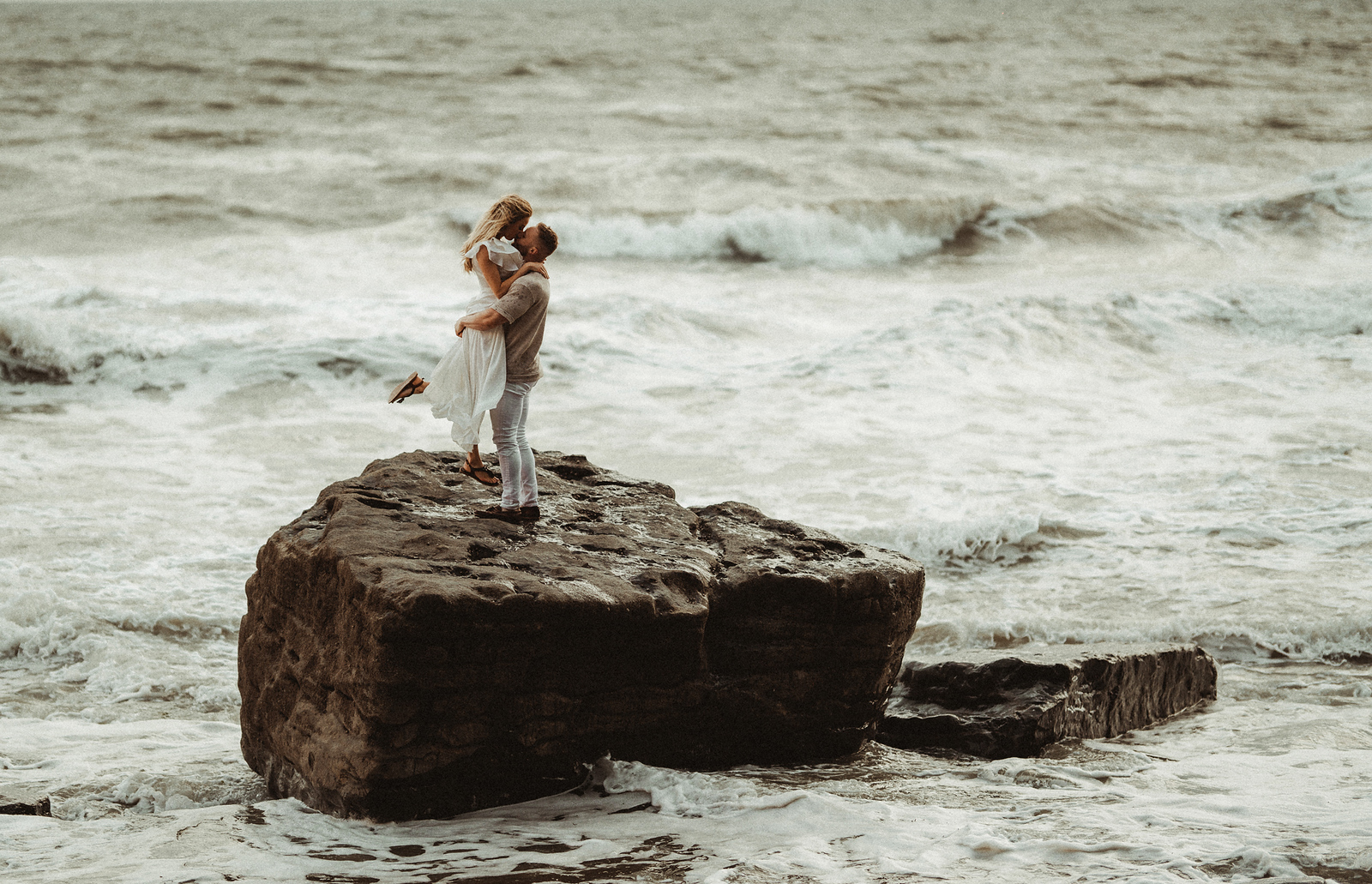 A couple on a rock in the middle of the sea