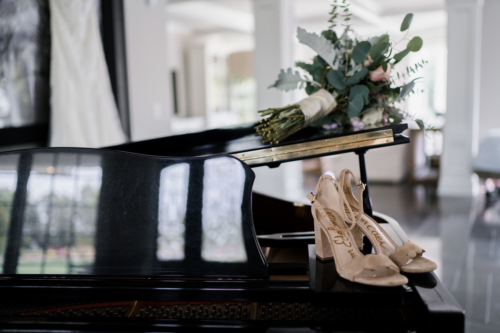 Brides wedding flowers and wedding shoes on a piano
