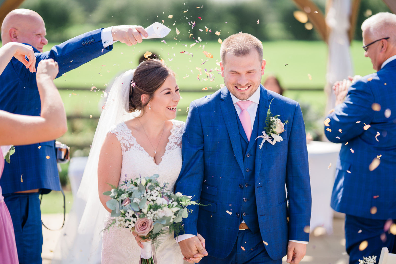 Bride and groom have confetti thrown over them by family and friends