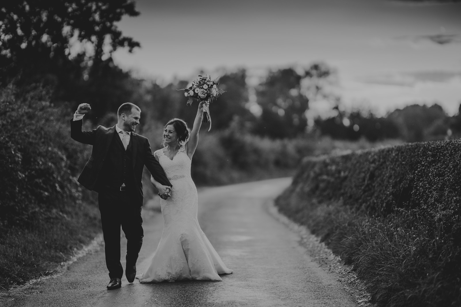 Bride and groom hold their hands in the air and smile at each other
