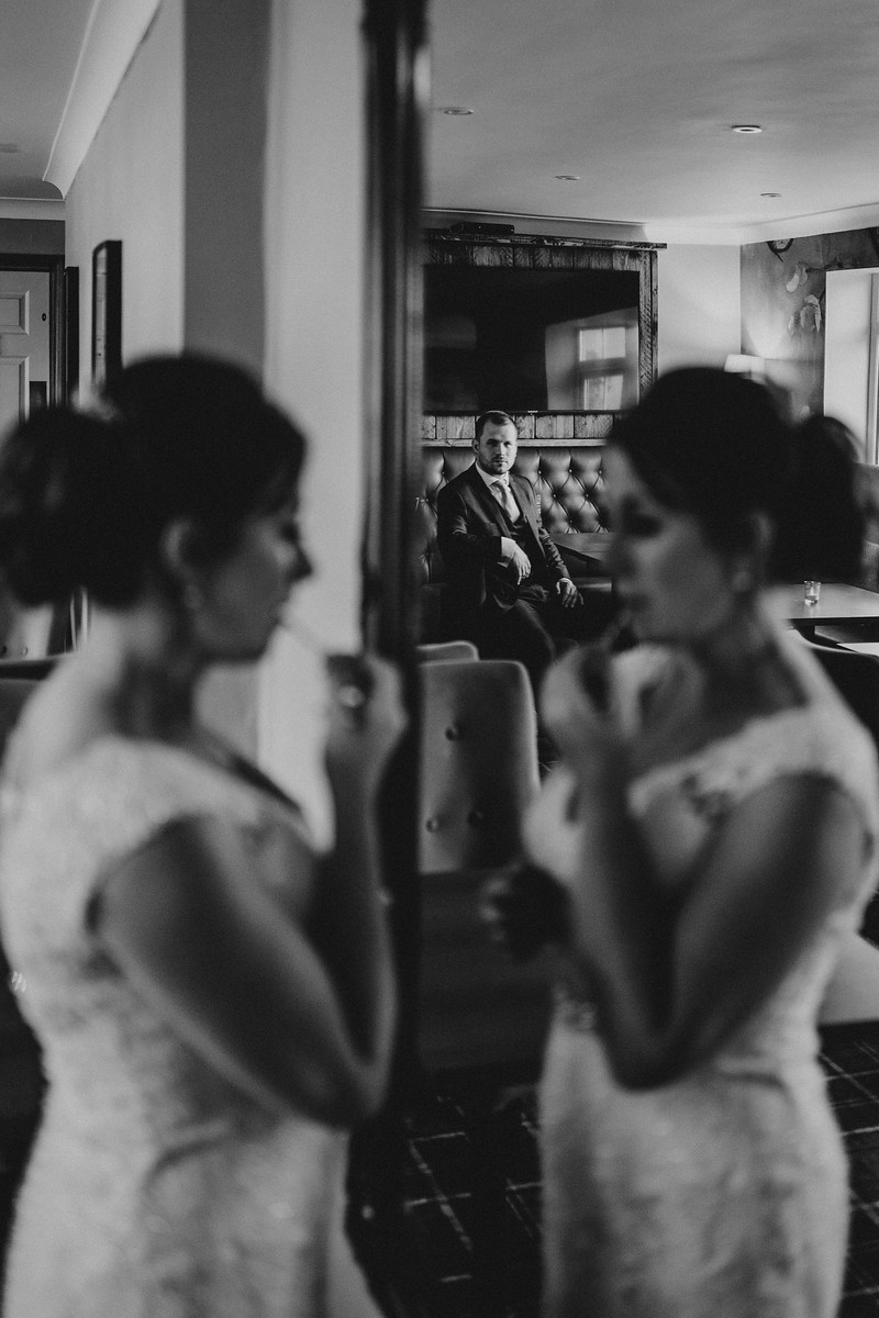 Bride is putting on her make up in the mirror as the groom is in the background watching