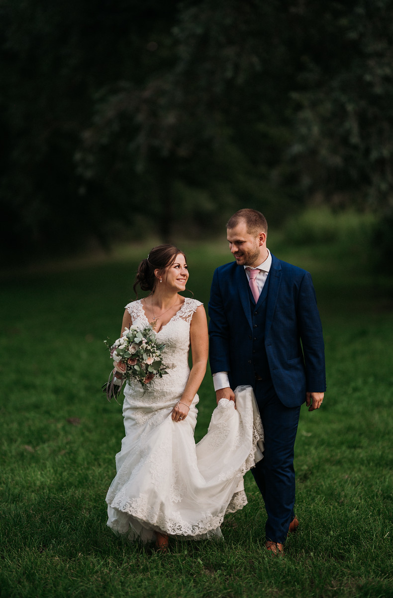 Bride and groom walk across the grass, smiling at each other