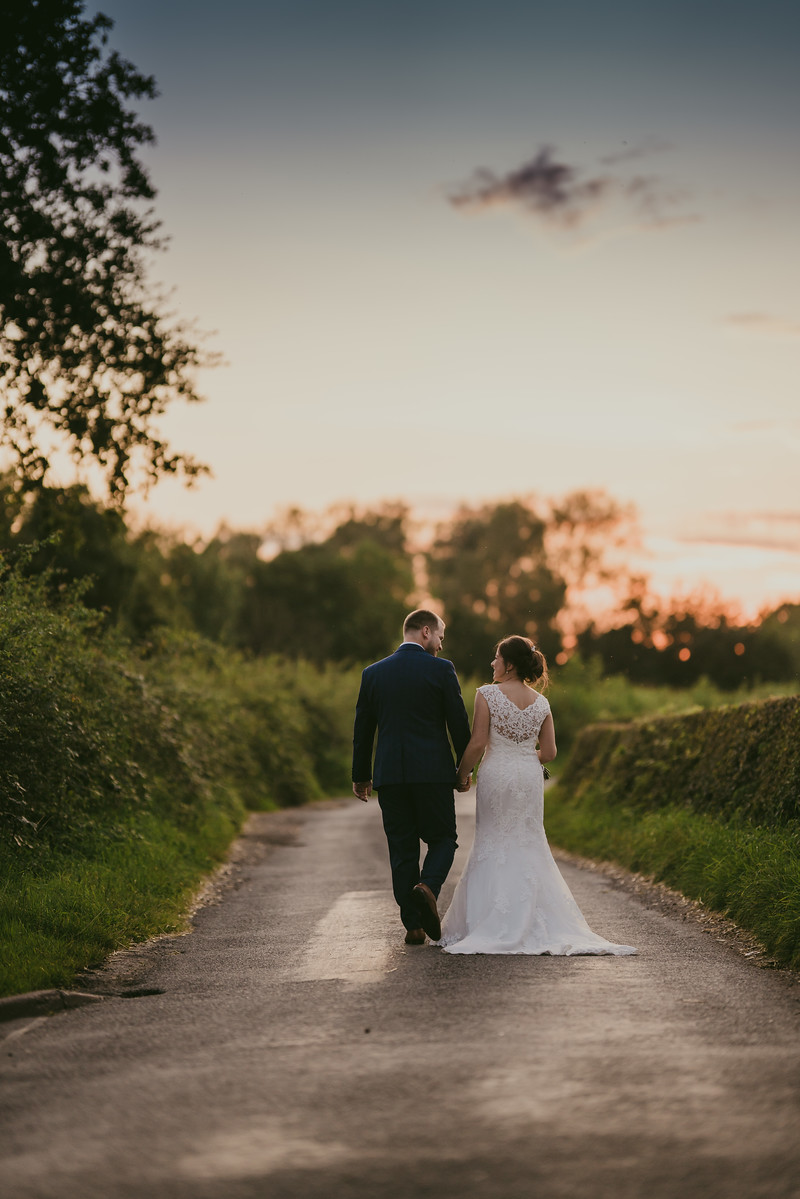 Bride and groom walk towards the sunset